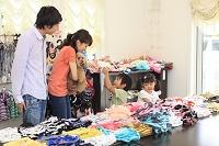ペットショップで犬の洋服を選ぶ日本人家族