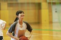 体育館でバスケットをする女子学生