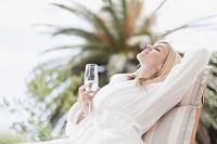 シャンパン片手にくつろぐバスローブ姿の外国人女性