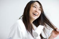 ドライヤーで髪を乾かしている日本人女性