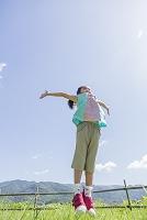 草原でジャンプをする女の子