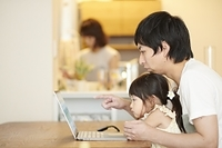 ノートパソコンを見る娘と父親