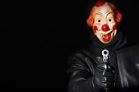 ピエロマスクでピストルを指す男性