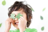 四つ葉のクローバーで遊ぶ日本人の男の子