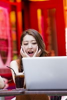 オープンカフェでパソコンを開く日本人女性
