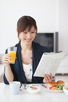 朝食時に新聞を読む女性