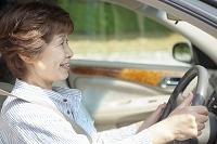 運転席に座る笑顔の日本人のシニア女性
