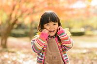 紅葉の公園で落ち葉で遊ぶ日本人の女の子