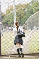部活動の様子を見つめる女子高生