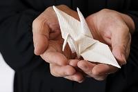 折り鶴を持つ喪服の女性