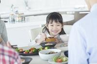 日本人家族と食事をする女の子