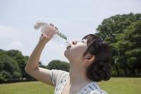 ペットボトルの水を飲む若い日本人女性