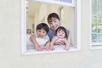窓から顔を出す笑顔の日本人親子
