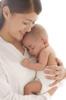 寝ている赤ちゃんを抱っこするお母さん
