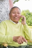 公園で電話するシニア男性