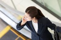 エスカレーターに乗る日本人ビジネスウーマン