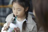 カフェで飲み物を飲む日本人の女の子