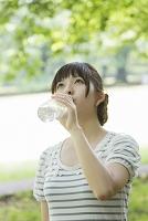 ペットボトルの水を飲む若い女性