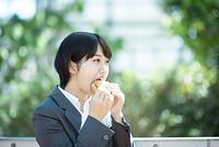 サンドイッチを食べるビジネスウーマン