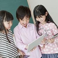 教室でタブレットを操作する日本人の小学生