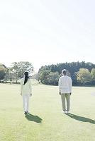 芝生の上に立つ後姿のシニア夫婦