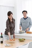 調理をする夫とお皿を運ぶ妻