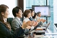 会議室で拍手をする日本人ビジネスパーソン