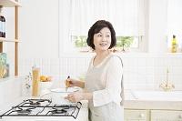 キッチンで料理をする日本人のシニア女性