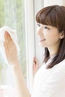窓拭きをする日本人女性