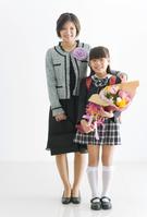 ランドセルを背負って花束を持つ女の子と母親