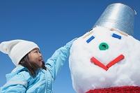 雪だるまの頭を撫でる子供
