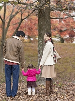 落ち葉の上で手を繋ぐ日本人家族