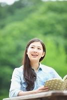 屋外で本を読む日本人女性