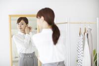 鏡を前に身支度をする日本人女性