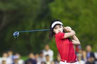 スイングする女子ゴルフ選手