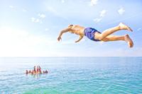 夏の海に飛び込む少年