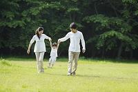 緑の中で遊ぶ小さな女の子と両親