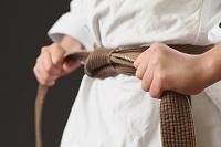 空手着の帯を締める日本人の子供