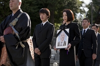 僧侶の後ろを歩く遺影を持つ日本人女性と遺族