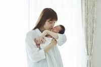 新生児を抱っこするお母さん