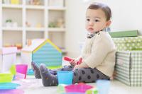 散らかった子供部屋に座る日本人の男の子