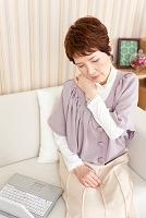 肩を押さえている中高年女性