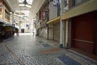 商店街にシャッターの絞められた店舗が見られる様子