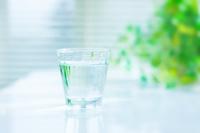 色いテーブルに置いたグラスの水