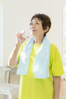 ガラスコップで水を飲むシニア日本人女性