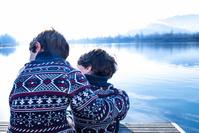 湖の岸に座る兄弟