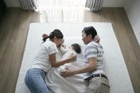 赤ちゃんと添い寝をする両親