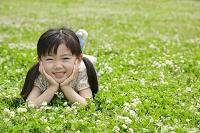 緑のクローバーの上で寝転がる日本人の女の子