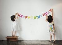誕生日の飾りつけをつる女の子