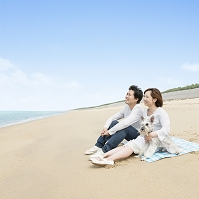 砂浜に座る日本人カップルと犬